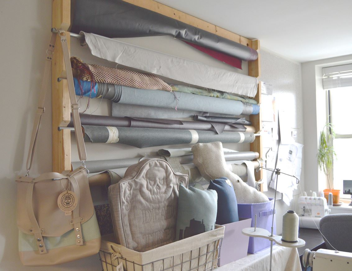 Fabric stored on rolls on wall display